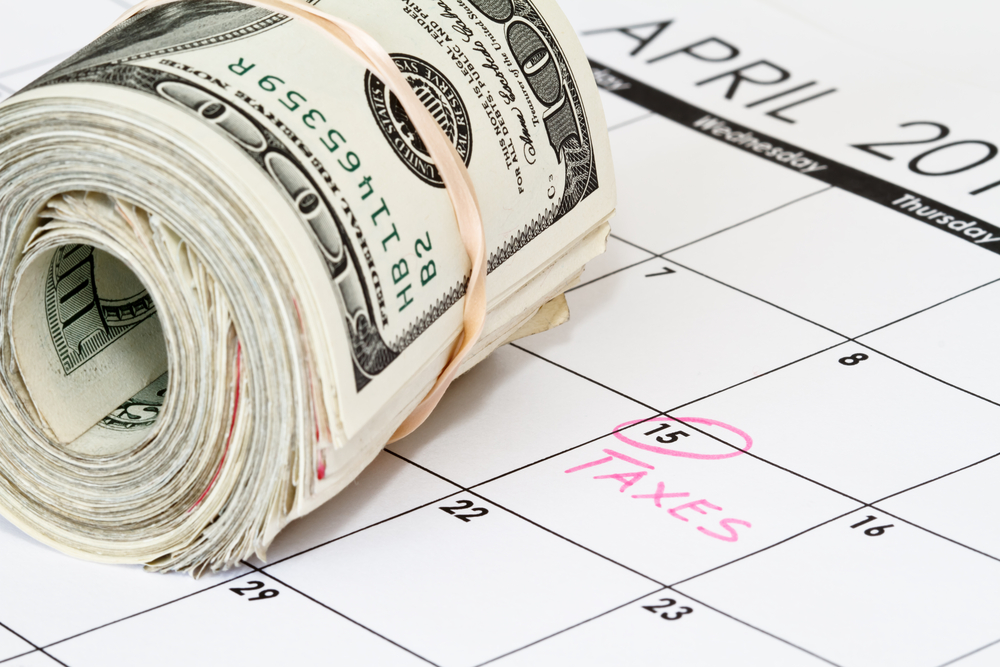 Roll of money on calendar with April 15 marked
