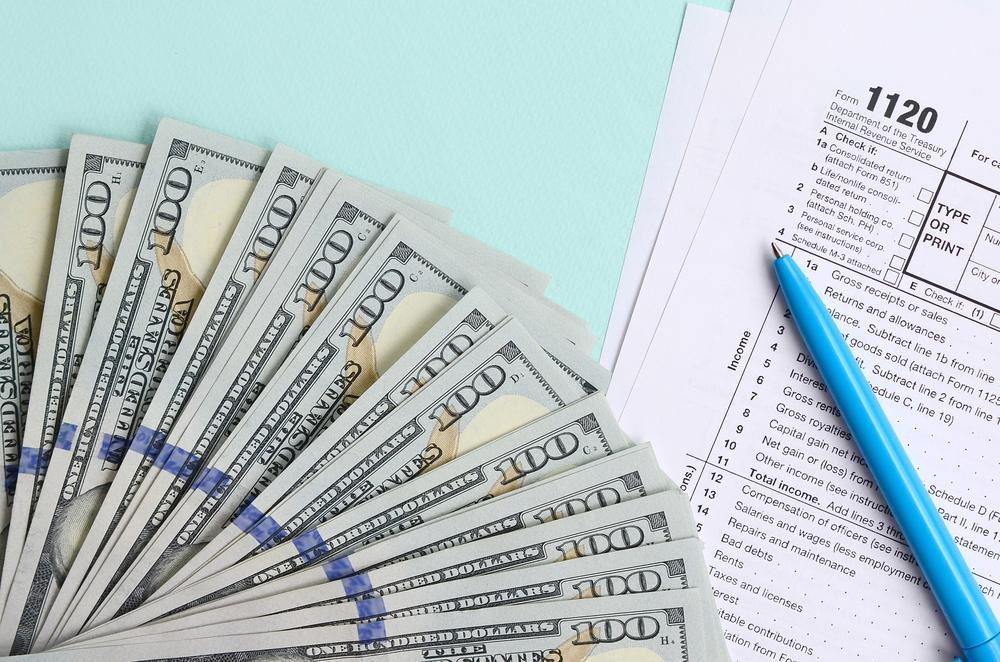 Hundred dollar bills next to tax form