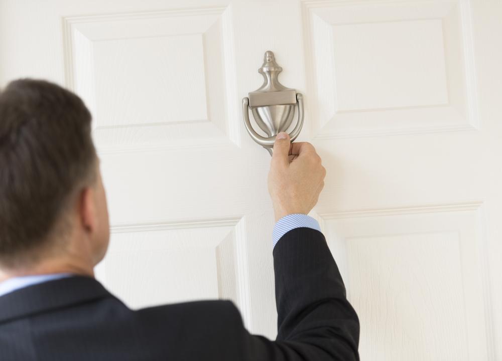 Businessman using door knocker