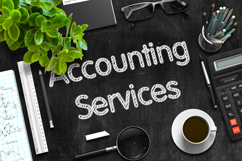 Accounting services on black chalkboard with bookkeeping tools