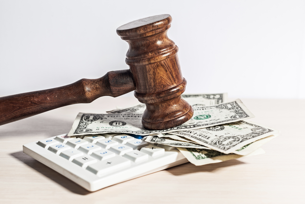 Gavel and money on top of calculator