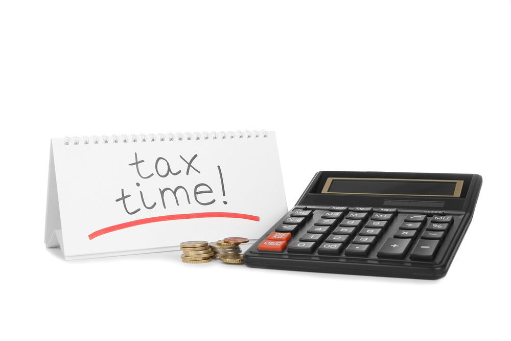 Tax time written on calendar beside calculator and coins
