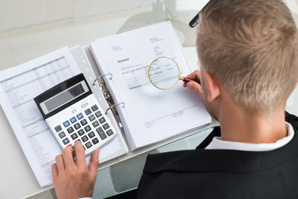 Businessman going through documents with magnifying glass and calculator