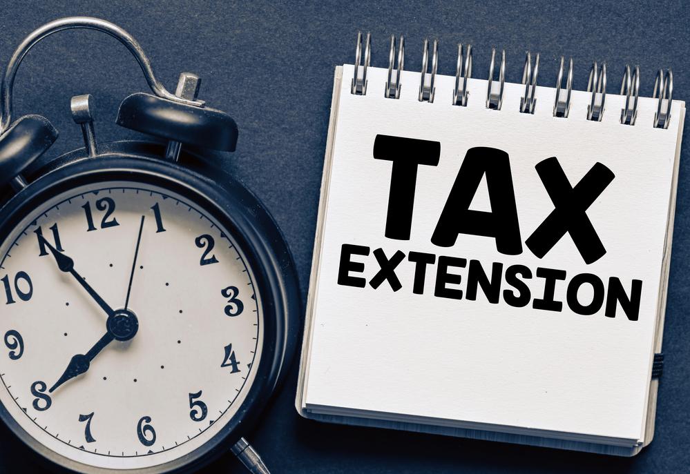 Tax extension written on notepad beside clock