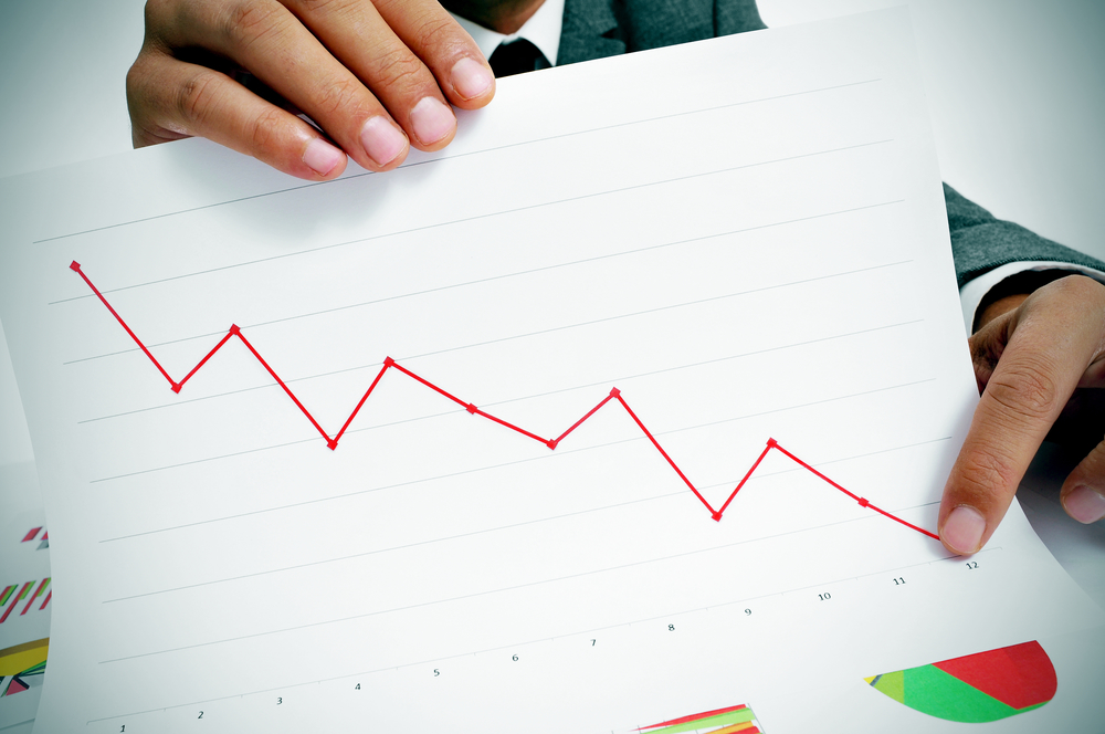 Man pointing to chart showing losses with pencil