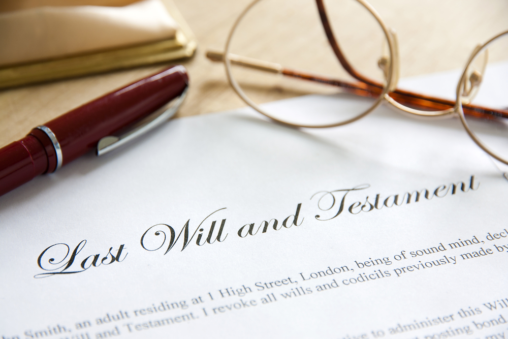 Last will and testament with glasses and pen