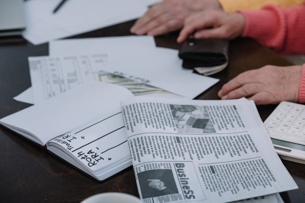 Couple with money, newspaper, and notebook comparing traditional and Roth IRA