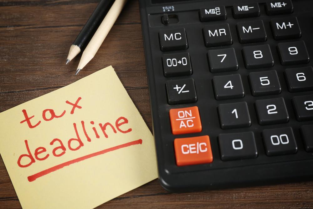 Tax deadline written on sticky note beside calculator