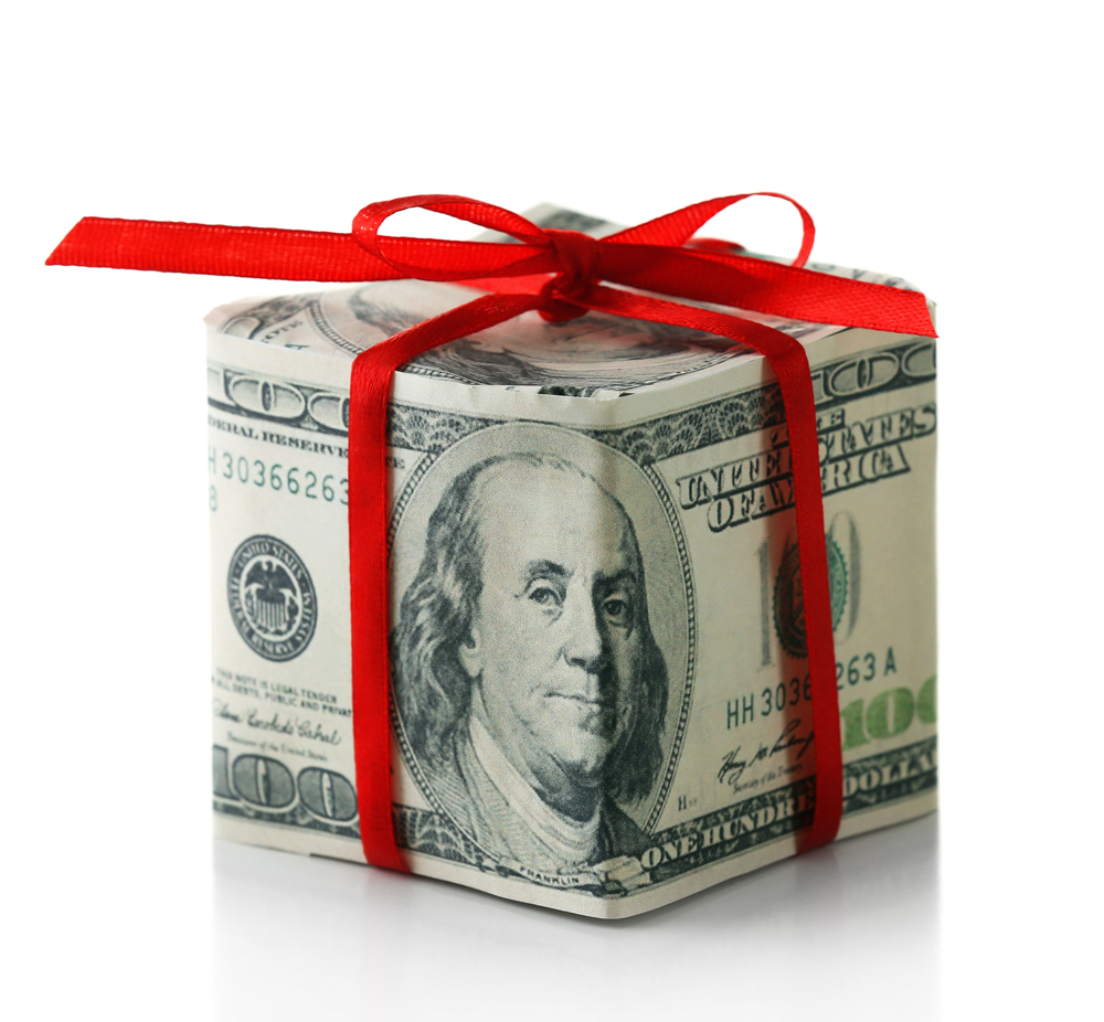 Hundred dollar bill folded like gift box with bow